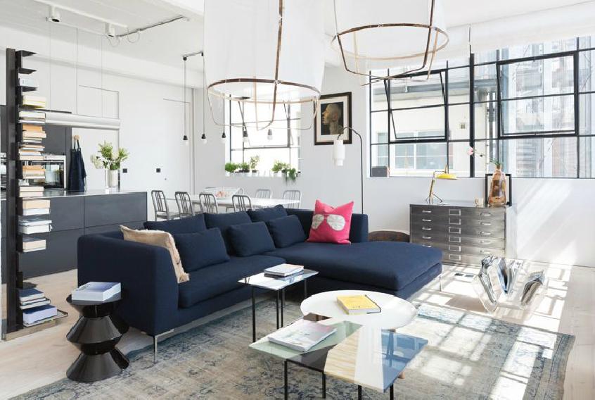 """A nagy belmagasság és az ipari hatás (látszódó csövek, vezetékek) ebben a londoni loftban is meghatározó stíluselemek, azonban a térszervezés """"amerikai konyhás"""". A konyha, nappali étkező egy légtérben kapott helyet és a bútorok """"húzzák meg"""" a határvonalakat (fotó: cloudstudios.co.uk)"""