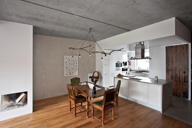A vasbeton födém és a kandalló minimalista, a csillár leleményes házibarkács, a konyha pedig ultramodern./Fotó: mode:lina architekci