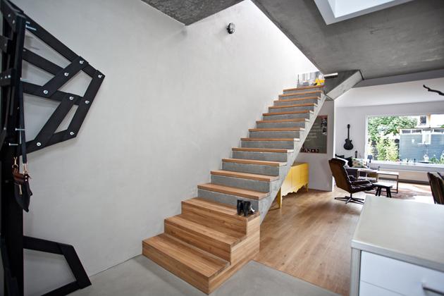 Az egyszerű vasbeton lépcső fa járófelületet kapott, az első három lépcsőfokot pedig oldalt is fával borították. Ez a játékosság megtöri a fehér-szürke hegemóniát./Fotó: mode:lina architekci