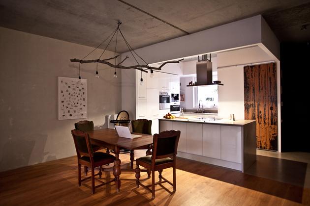 A konyha egy légtérben van a nappalival és az étkezővel, ám a burkolatok és a konyhasziget határolja./Fotó: mode:lina architekci