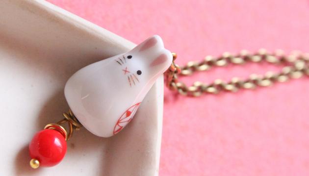 Vadjutka nyuszis ékszere: porcelán nyúl és piros üveggyöngy.