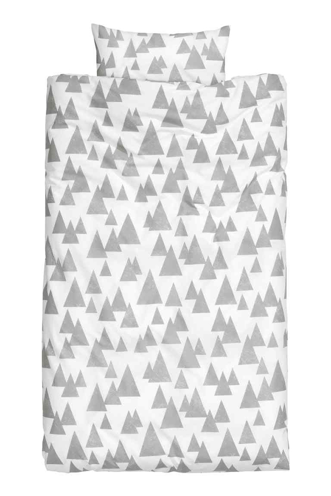 Tulajdonképpen fehér alapon szürke háromszögek, mégis ez a minimalista fenyőerdő varázslatosan szép./H&M