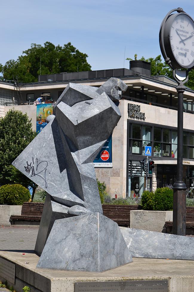 A háttérben az egykori buszpályaudvar, a mostani Design Terminál, ami ki tudja mi lesz egy év múlva. Előtérben Sztehló Gábor emlékműve, amelyet 2009-ben készített Víg Tamás. De tudod, ki volt Sztehló Gábor? (Fotó: Myreille, 2016)