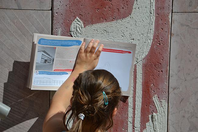 """A Városi Titkos Füzet nem csak információt közöl, hanem játékra is csábít és """"közel"""" hozza az épített környezetet. A füzet egyik feladata, hogy rajzold (képzeld) tovább a Gödör, ami most már Akvárium egyik lejáratának falán látható Tarczali Dávid beton domborművét. Az pedig már csepp pikantéria, hogy a füzethez mellékelt matricákkal újra lehet tervezni és fásítani a József Nádor teret, de közben az is kiderül, ki is az a nádor. (Fotó: Myreille)"""