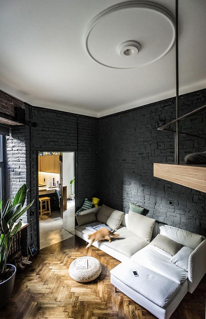A nappalit utalja a grafitszürke fal, a világos kanapé és a gyönyörű fa padló